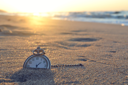 stop watch in sand on shore with sunset