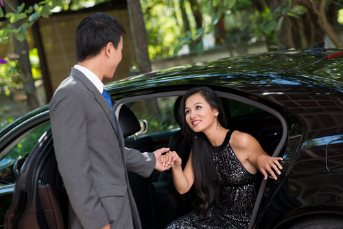 Romantic man helping his lady out of the car